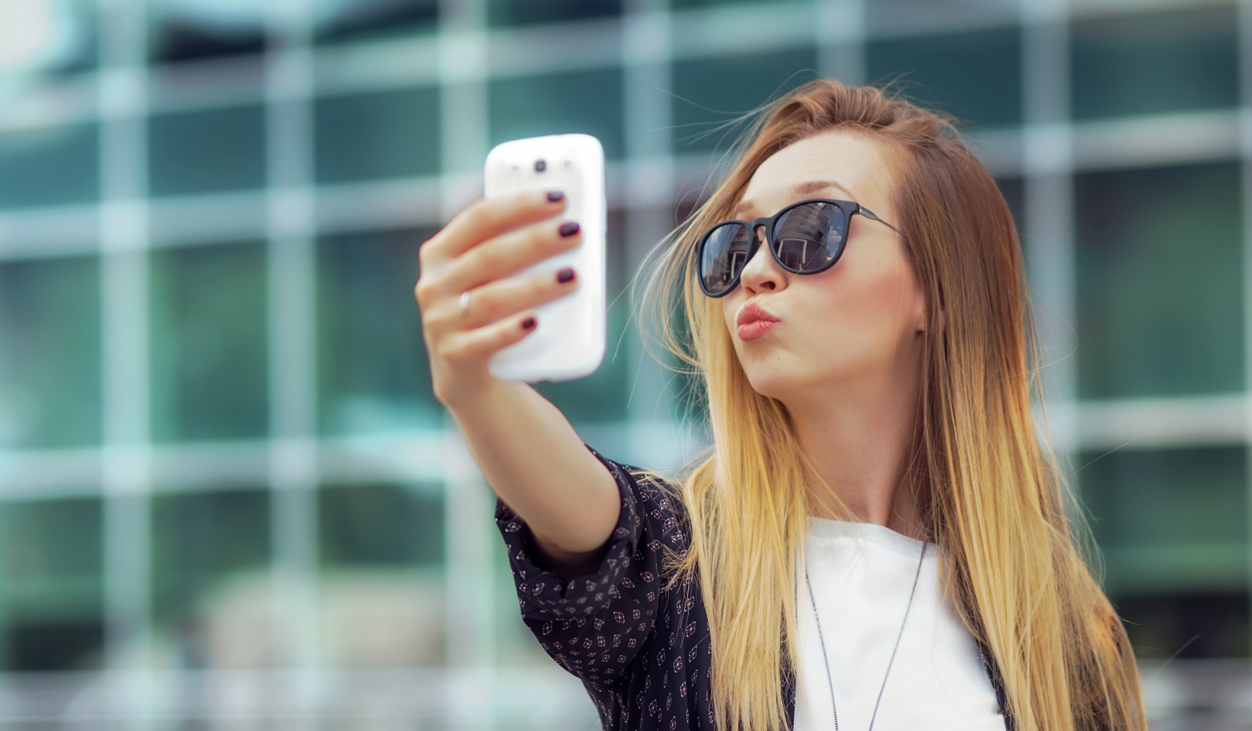 Young happy girl make a selfie with his smartphone, outdoors