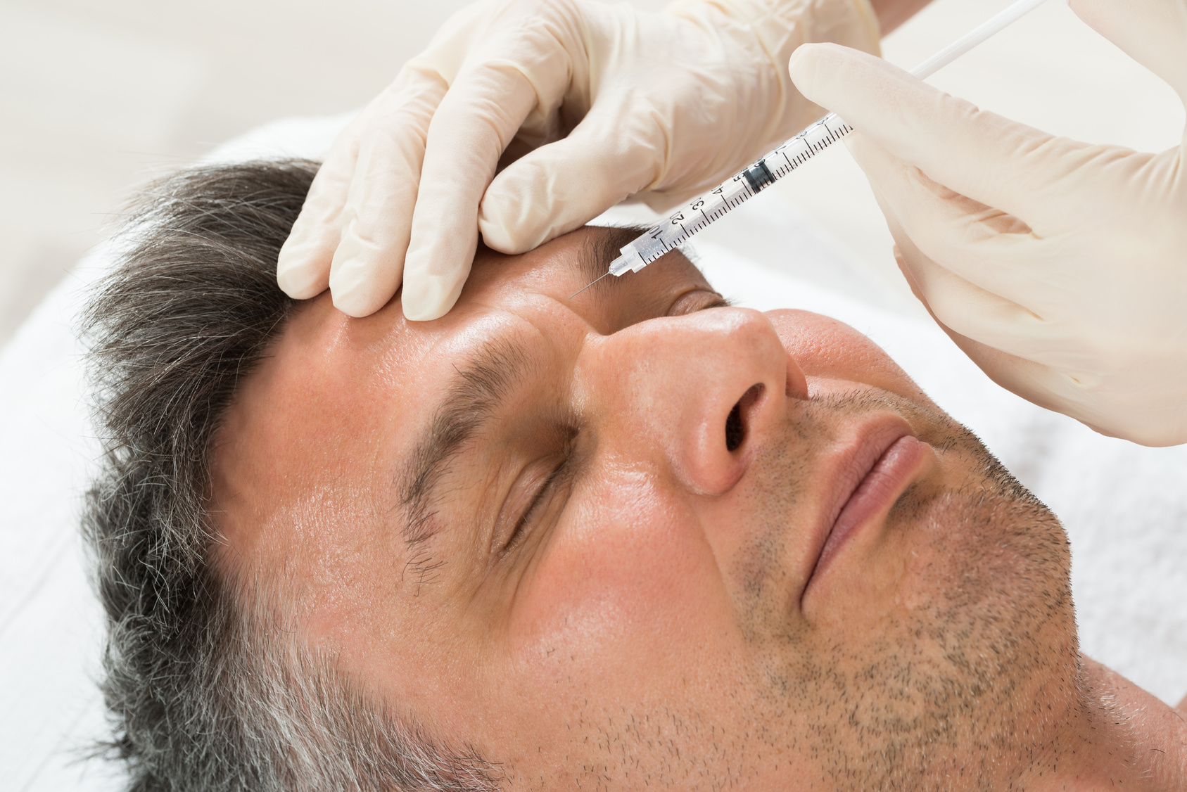 Mature Man Receiving Cosmetic Injection With Syringe In Clinic